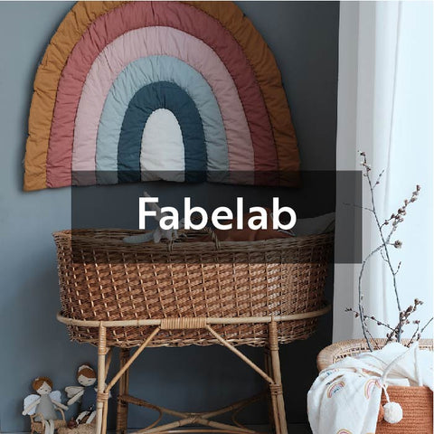 Nursery featuring a rattan moses basket and rainbow wall hanging