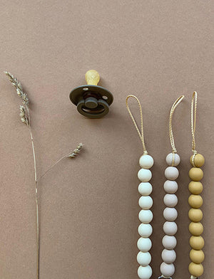 Flat lay showcasing three Bezisa beaded pacifier clips with a pacifier on a brown background