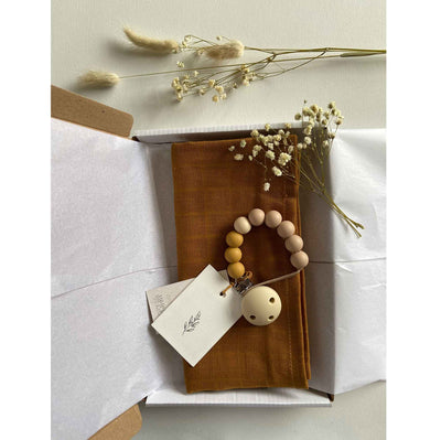 Flat lay of a gift box which includes a beaded dummy clip and an organic cotton muslin square