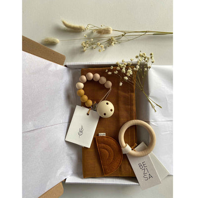 Flat lay of a gift box which includes a beaded dummy clip, sunset teether and an organic cotton muslin square