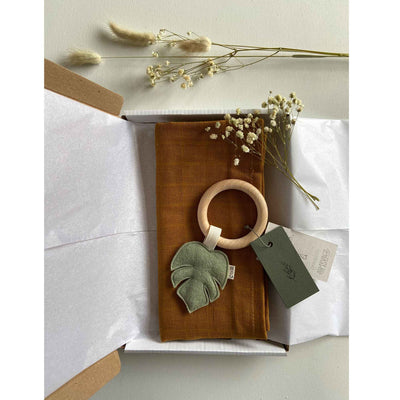 Flat lay of a gift box which includes a monstera leaf teether and an organic cotton muslin square