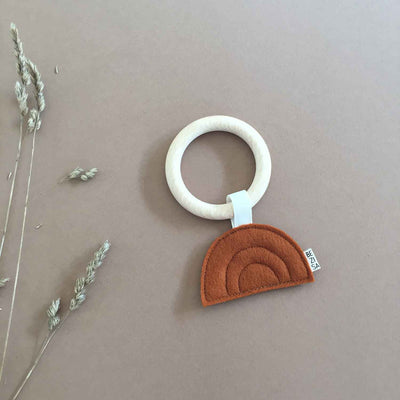 Felt burnt orange sunset on a wooden teething ring on a brown background next to a dried flower