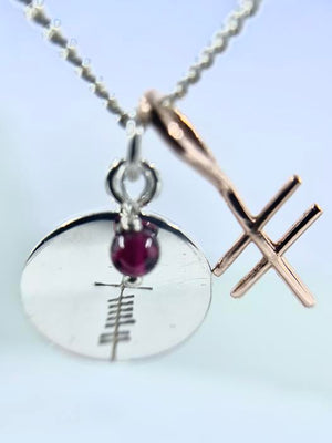 love coin  with garnet with gold ogham inital