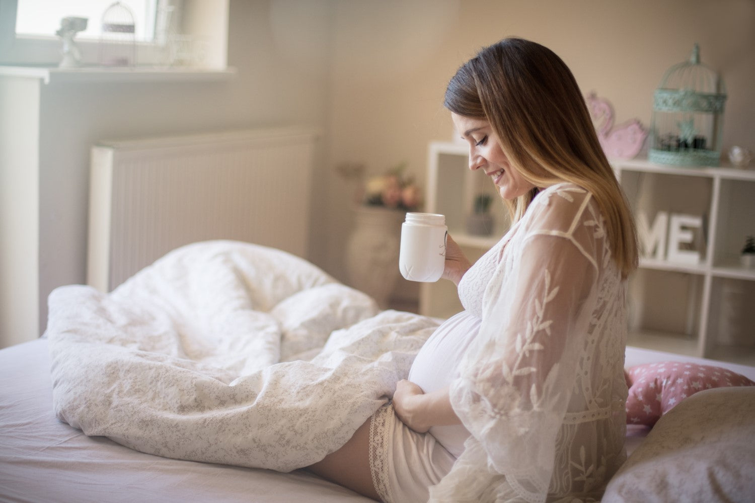 pregnant woman drinking coffee in bed
