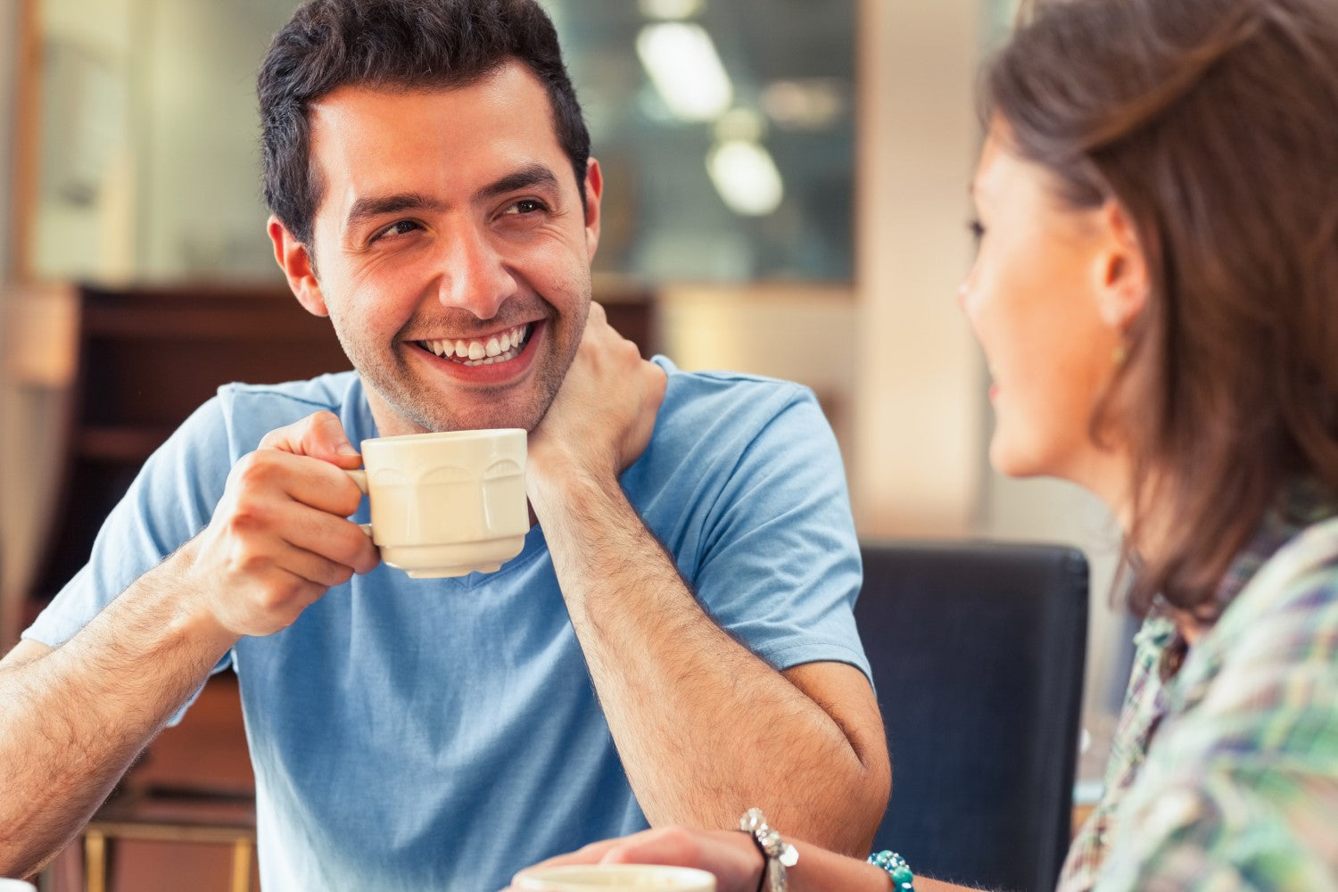 man talking to a lady while drinking a coffee