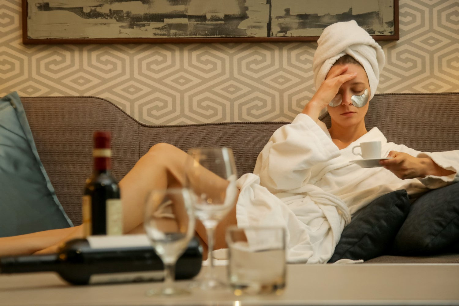 lady holding a cup of coffee after bath with alcohol on the table in front of her