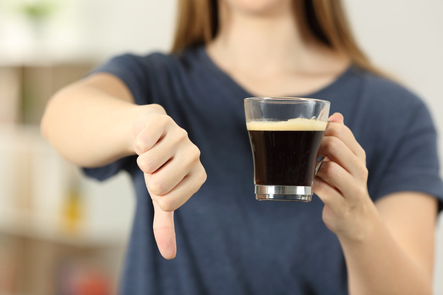 woman holding coffee with thumbs down