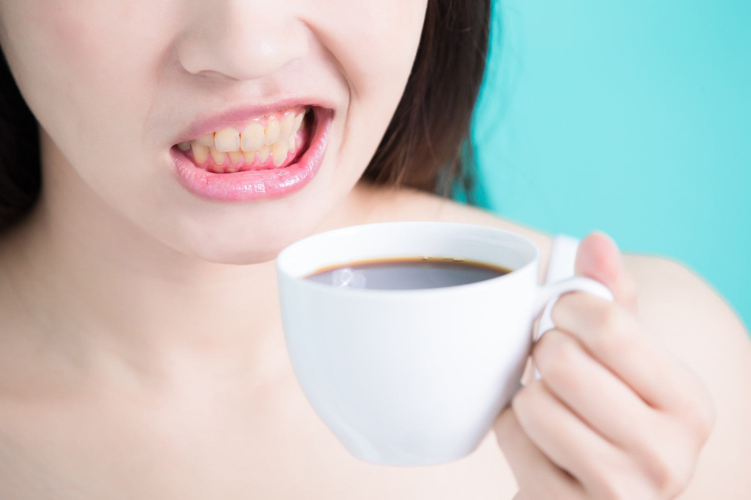woman showing her teeth while holding a coffee
