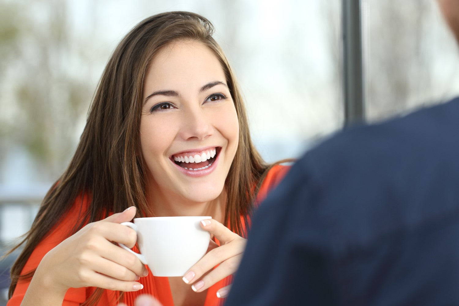 lady laughing with holding a coffee