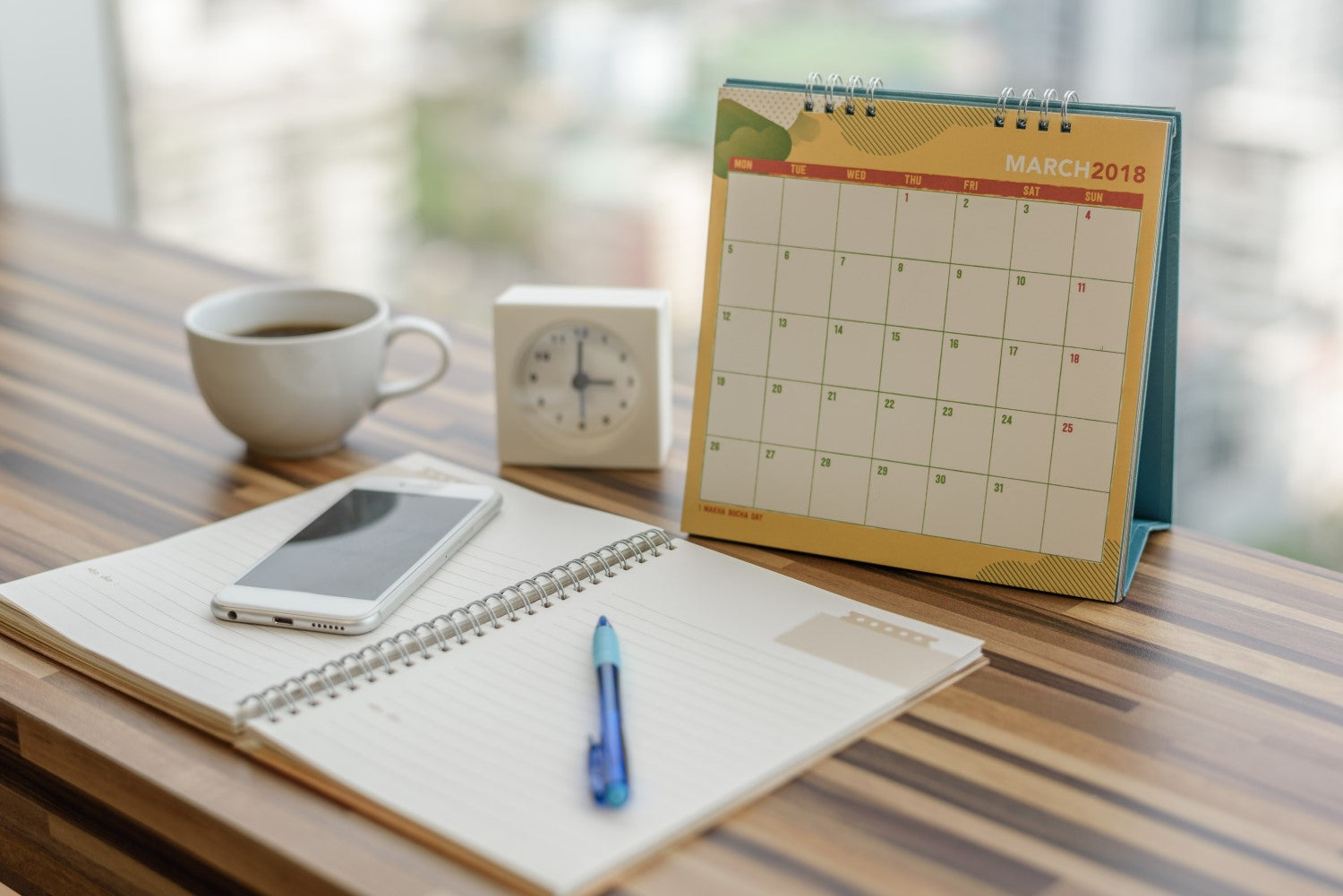coffee,clock, calendar, notebook, pen and phone on a table