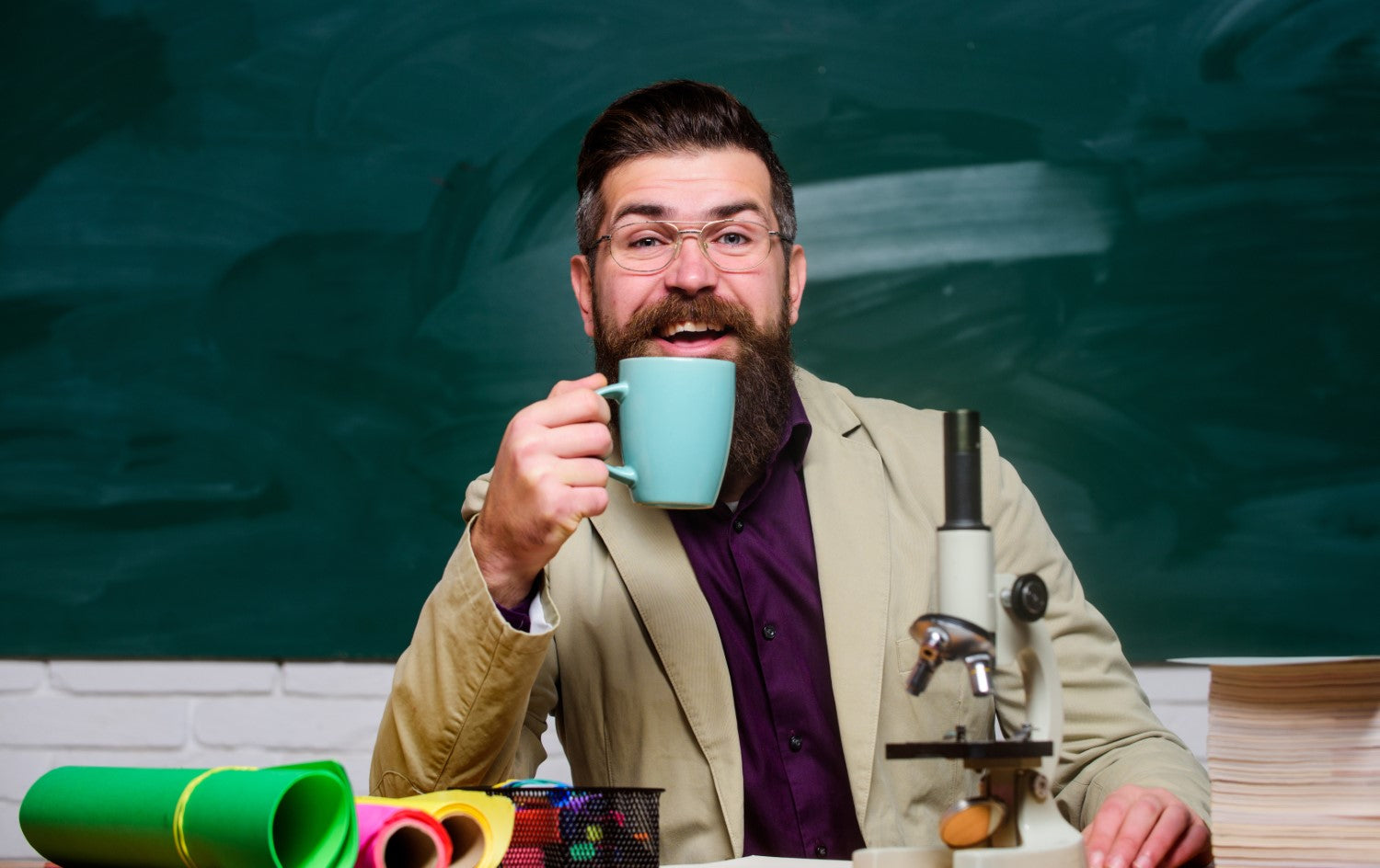 man holding coffee with microscope in front