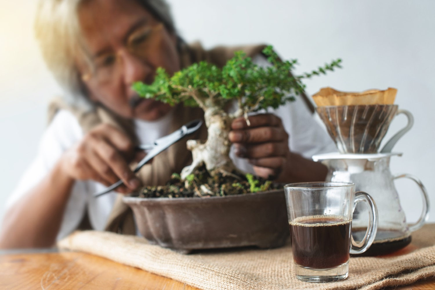 old man taking care of the plants with coffee on the side