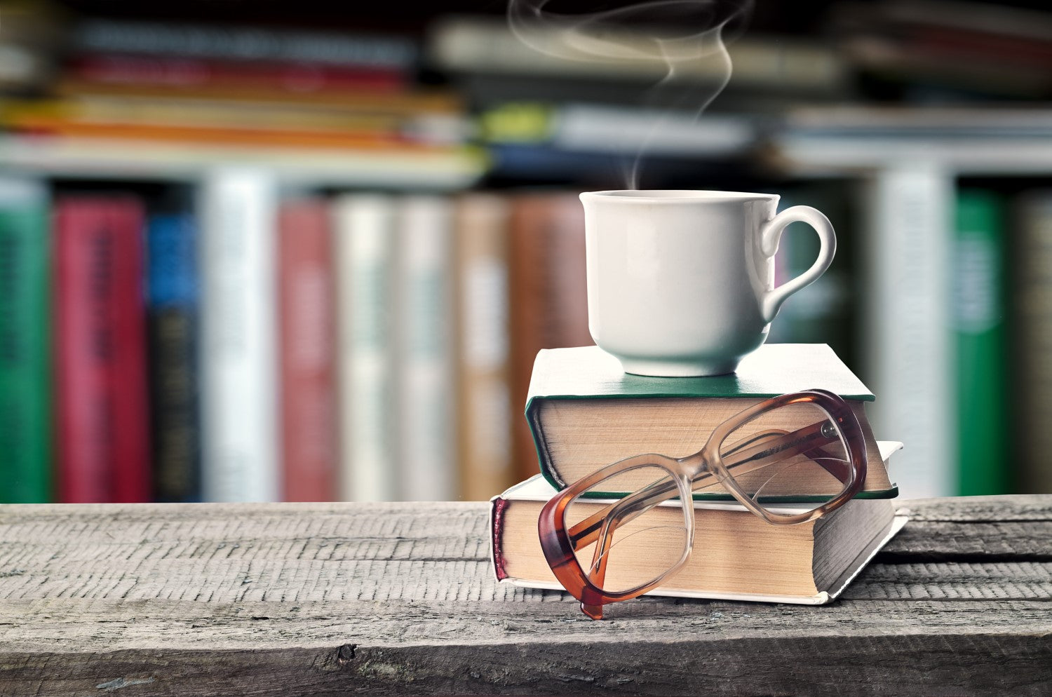 cup of coffee above the book with eyeglass in front