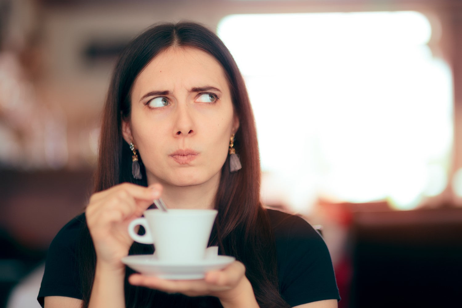 woman thinking while having a coffee