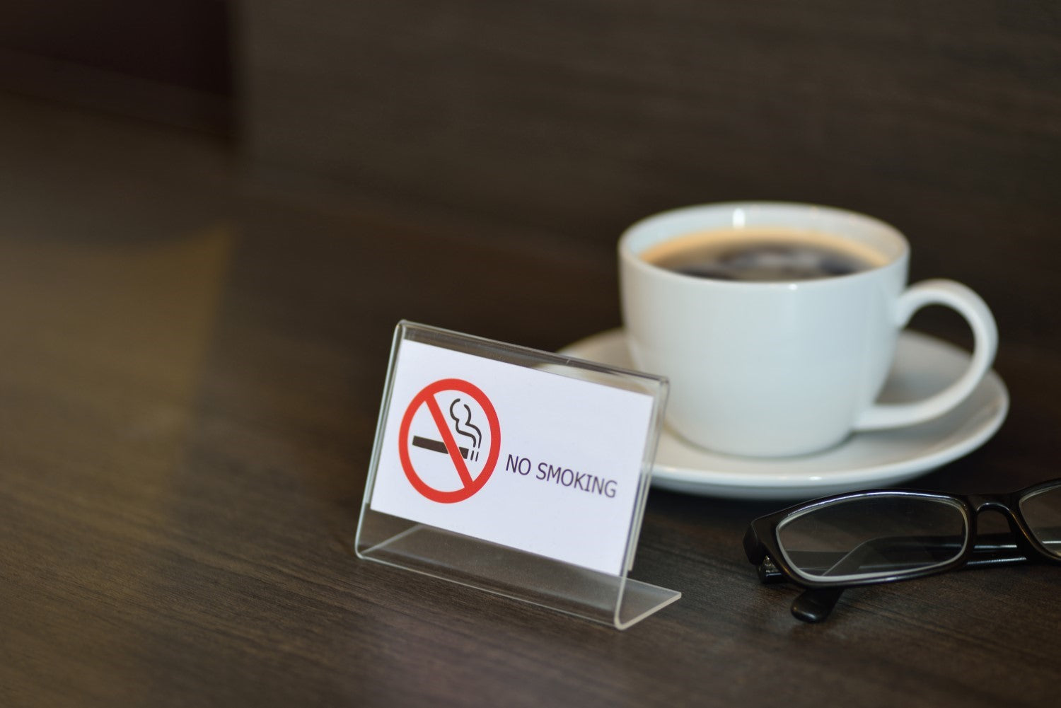cup of coffee with no smoking sign