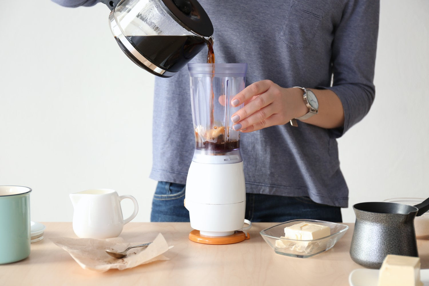 pouring black coffee on blender
