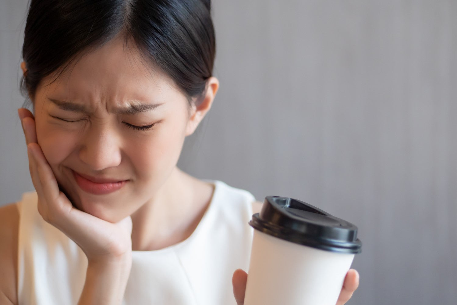 lady with toothache having a coffee