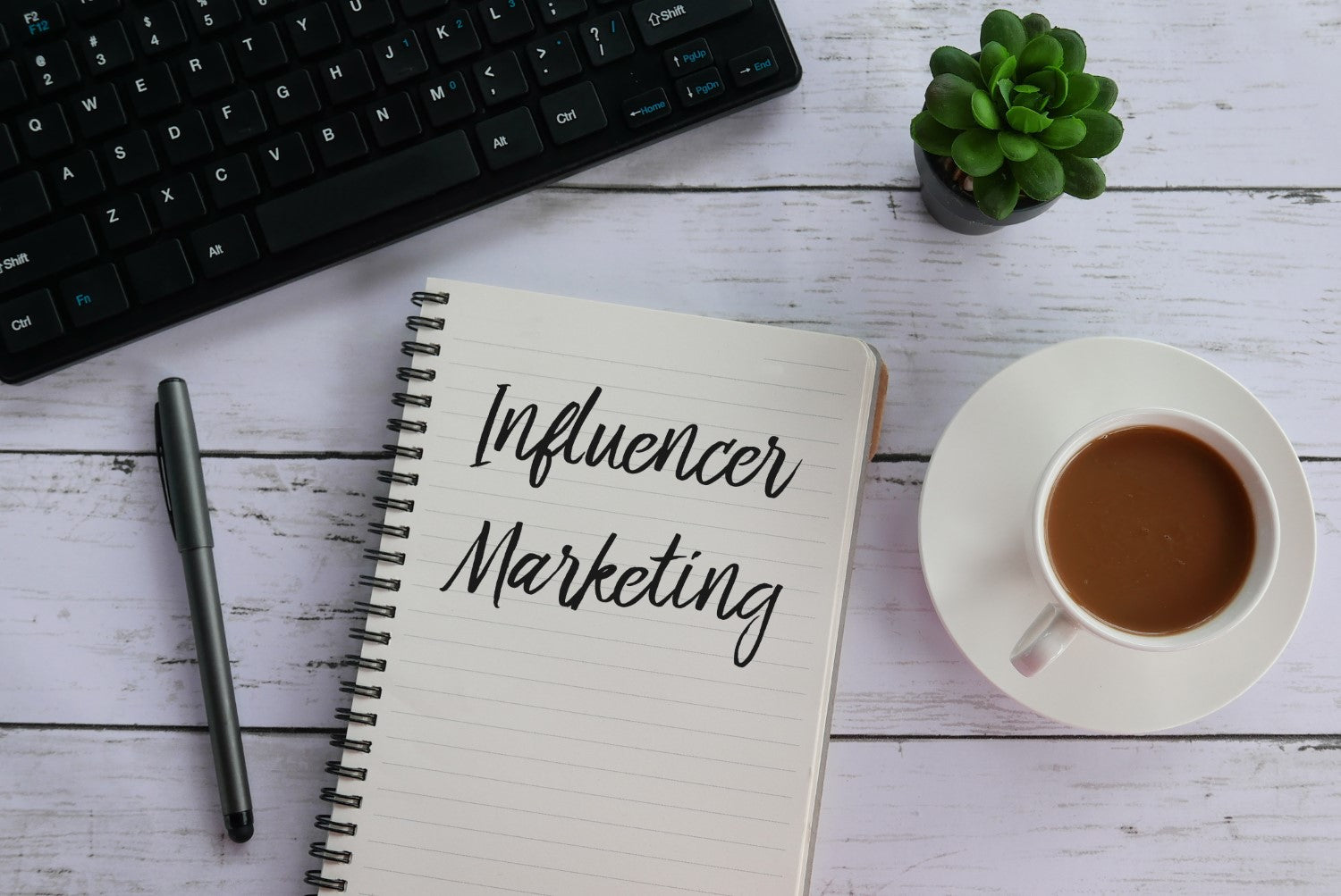 influencer marketing, cup of coffee, plant and pen