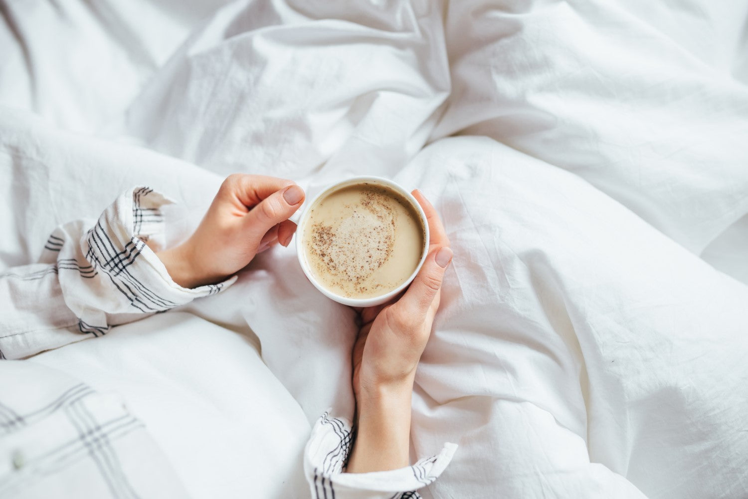 holding coffee on bed
