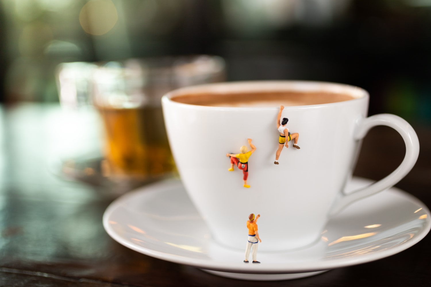 cup of coffee with small people climbing