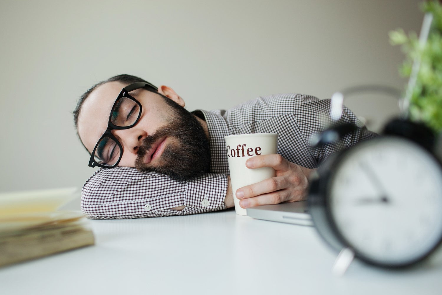 man sleeping while holding on a coffee