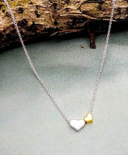 Load image into Gallery viewer, necklace with one silver heart and one smaller gold heart to the right. the chain runs through them.