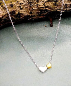 necklace with one silver heart and one smaller gold heart to the right. the chain runs through them.