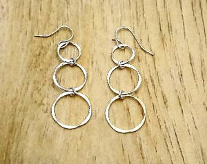 Silver earring with 3 circles dangling in a line. 2 inches long. Light and casual. Made in USA