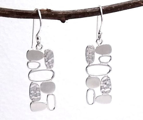 sterling dangle earring with ovals put together to form a rectangular shape. two hammered, three high shine, and three cutout ovals make up each earring.