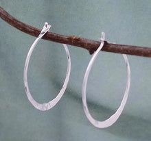 Load image into Gallery viewer, Hammered hoops with peg-in-hole style closure resting on a vine