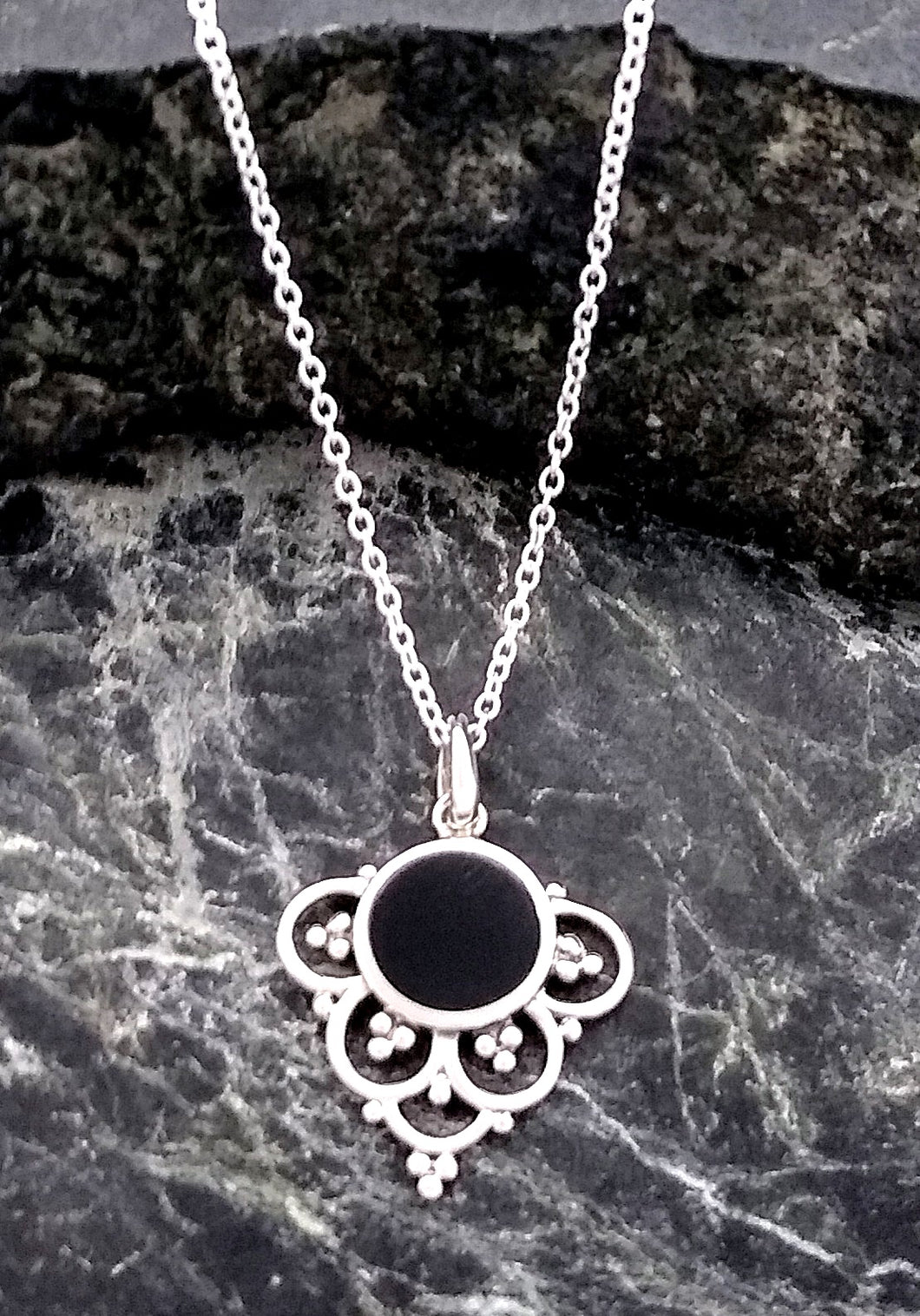 circular onyx pendant with 4 circles and a semi circle forming an arch around it's bottom half with small spheres to accent inside the circles.