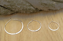 Load image into Gallery viewer, Shows 3 sizes of pounded silver hoops. 1.5 inches, 1 inch, 3/4 inch