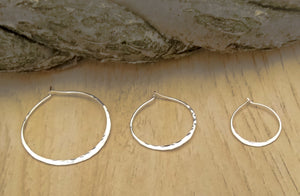 Shows 3 sizes of pounded silver hoops. 1.5 inches, 1 inch, 3/4 inch