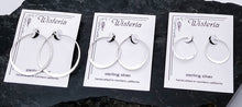 Load image into Gallery viewer, three sets of sterling silver hammered hoops, descending in size on Wisteria brand earring cards.
