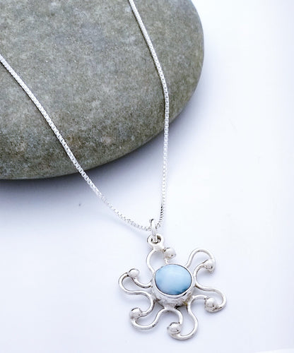 Sterling sun pendant with a circular larimar stone at center. 6 wire sunrays curve to their right and each has a silver ball at the end.