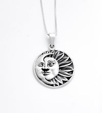 Load image into Gallery viewer, A circular pendant of a half sun with a face and 13 flower-petal-like rays extending to the right. A crescent moon with a face covers the left side.