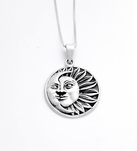 A circular pendant of a half sun with a face and 13 flower-petal-like rays extending to the right. A crescent moon with a face covers the left side.