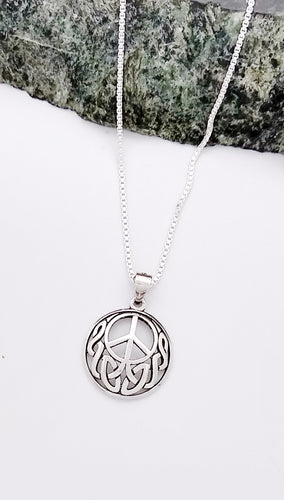 circular pendant with a peace sign and celtic knotting underneath