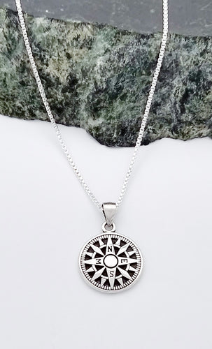 a circular sterling pendant of a compass with the 4 cardinal directions noted with their letters. There are three points between each of the cardinal directions and a blackened background.
