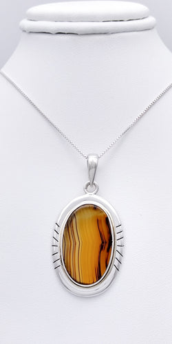 A translucent orange-brown oval stone with black striations going vertically through it is set in a sterling silver pendant with 7 lines etched on the right and left sides