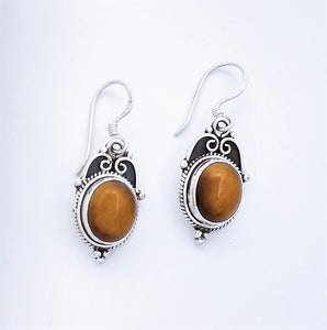 Oval Tiger Eye stone set in sterling silver earring. Braid detail around the edge with three balls in a pyramid shape at the bottom. Top has two curled arches with blackened background.