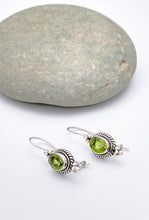 Load image into Gallery viewer, Sterling silver drop earrings with braiding around the side and three spheres in a triangle shape underneath and atop the peridot stone. Wire hooked in back