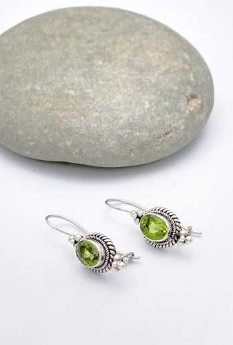 Sterling silver drop earrings with braiding around the side and three spheres in a triangle shape underneath and atop the peridot stone. Wire hooked in back