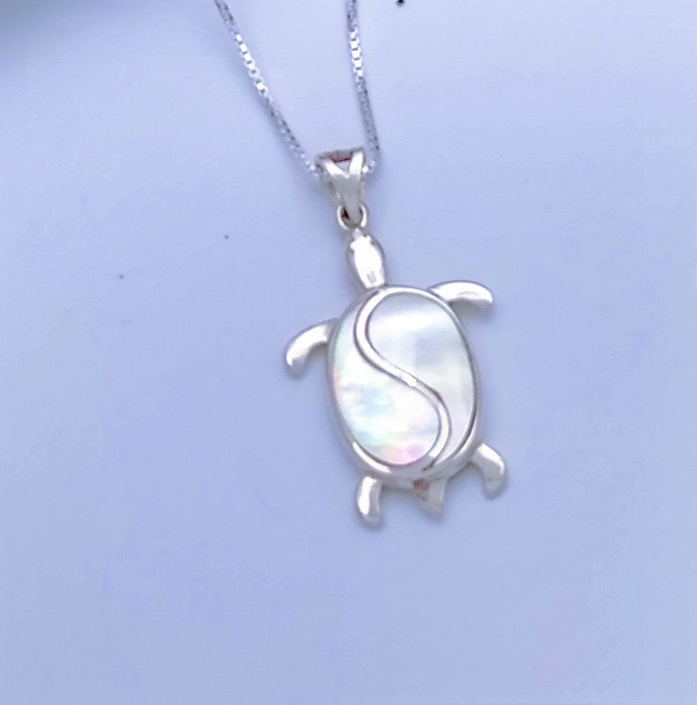 Sterling silver turtle pendant with an S-shape down the center of its back. Mother of pearl on either side of the S create the full shell.