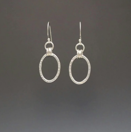 textured silver oval earrings with three rings connected to another small ring on a french wire