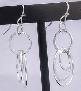 A silver french wire holds a silver hoop with 3 various sized hoops connected to it