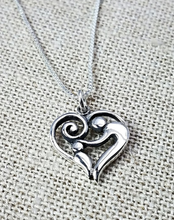 Load image into Gallery viewer, Sterling silver pendant of a heart with an adult patting the head of a child inside.