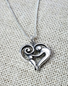 Sterling silver pendant of a heart with an adult patting the head of a child inside.