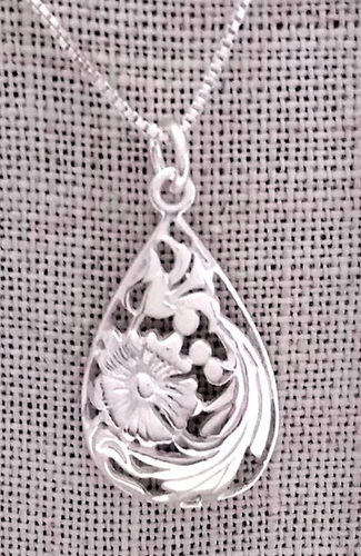 Domed teardrop shaped pendant with cutouts to show image of flowers and leaves