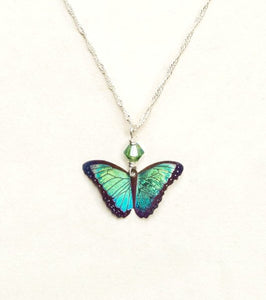 A bright green butterfly pendant with green bead on a silver chain